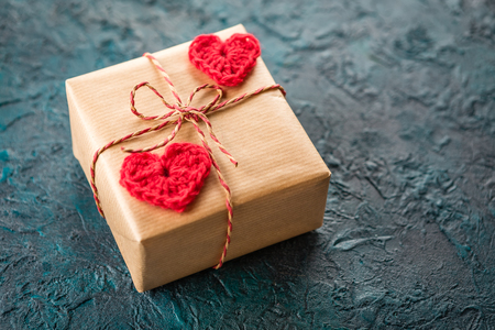 Gift boxes and crochet valentine hearts on dark bacground. Stock Photo