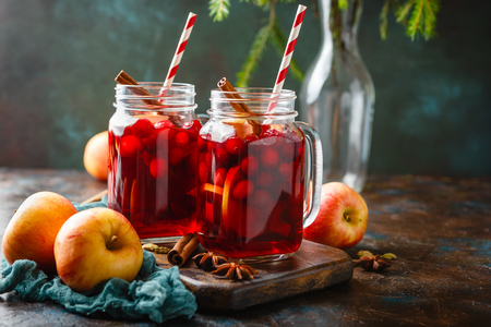 Two glass jars with a hot Christmas drink made from cranberries and apples with spices, mulled wine, punch or grog.