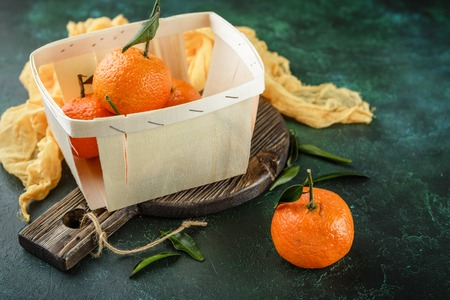 Basket with fresh tangerines on a dark green background Stock Photo