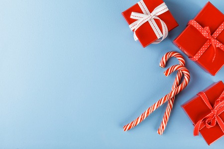 Christmas red gift boxes and Candy canes onblue background. Top view with copy space Stock Photo