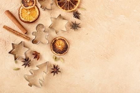 乾燥オレンジのスライス、シナモン棒、星アニス、カルダモンの種子と明るい背景にクリスマス クッキー金属用のニッパー