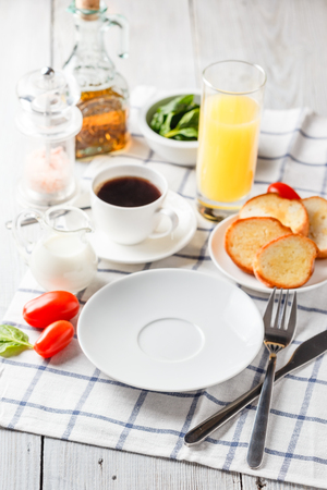White plate, coffee and orange juice on a white wooden table. Serving for breakfast