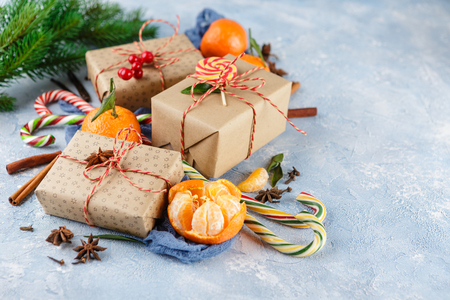 Fresh mandarins with leaves, candy canes, gift boxes in kraft paper and spices - cinnamon, anise and cloves on a blue background