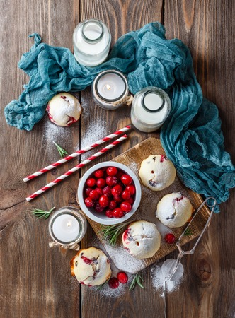 Muffins with cranberries and chocolate, bottles with milk and paper straws and candles on a dark wooden table. Top view Stock Photo