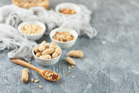 Set of different types of nuts - peanuts in shells, pine nuts and homemade granola in glass jar on gray background