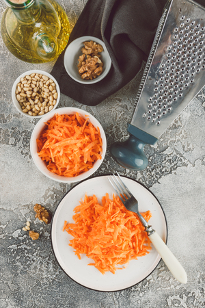 Ingredients for a salad of grated carrots with pine nuts on a black background. Top view with