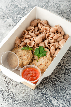Pasta Conchiglie from wheat with burger cutlets and sauce in lunchbox on gray background. Healthy food delivery.