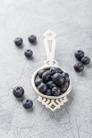 Blueberries or bilberries in an antique tea strainer on grey background. Delicious juicy fresh organic berries. Healthy eating and nutrition concept Archivio Fotografico