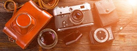 Old film camera, lenses and old exposure meter on a wooden background. Horizontal photo banner for website header