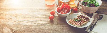 Halloumi grilled cheese with grilled bell peppers, rose wine, tomatoe and arugula. Banner for website header design with copy space for text