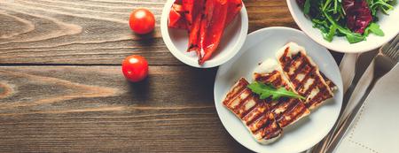 Halloumi gegrilde kaas met gegrilde paprika, tomaat en rucola. Bovenaanzicht, banner voor koptekstontwerp van de website met kopie ruimte voor tekst