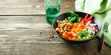 Colorful Buddha Bowl with chickpeas, carrots, tomatoes, cucumbers, radish and peppers on a wooden table. Vegetarian salad. Space for text. Long wide banner