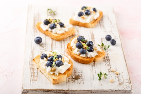 Toast crostini with fresh berries blueberry and honey, Ricotta cheese, thyme and hazelnuts, over white wooden textured board. Top view, copy space.