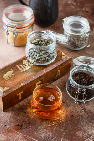 Glass cup of hot tea with jars of different kinds of tea - black, green, herbal and wooden box for tea