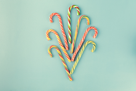 Sweet Candy canes on blue background. Flat lay. Top view.