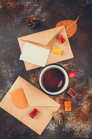 Enamel cups of tea, watercolors in cuvettes, two envelops, greetings card, autumn leaves and bumps on a rusty brown background Foto de archivo