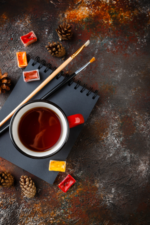 Red enamel cups of tea, watercolors in cuvettes, brushes and bumps on a rusty brown background