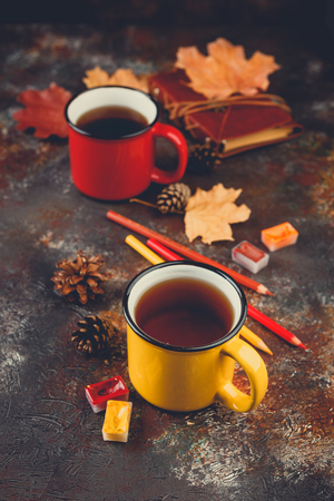 Yellow and red colored enamel cups of tea, watercolors in cuvettes, colored pencils, autumn maple leaves and bumps on a brown background