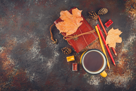 Yellow enamel cups of tea, watercolors in cuvettes, colored pencils, autumn maple leaves and bumps on a brown background