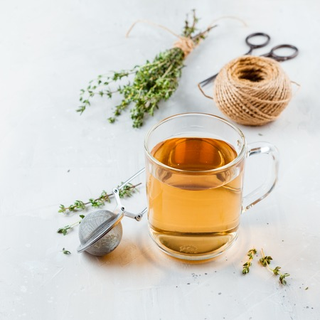 Transparent glass cup of herbal tea with thyme and sprigs of thyme tied in a bunch on a white background