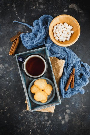 Blue enamelled cup of tea, cinnamon sticks, anise stars and shortbread on a dark background. Top view.