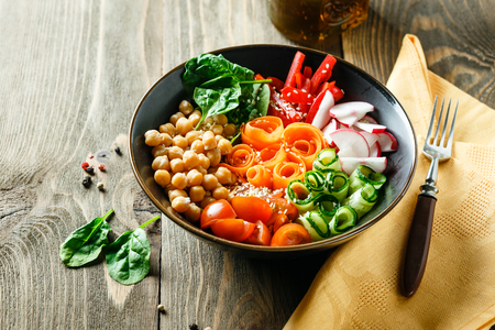 Colorful Buddha Bowl with chickpeas, carrots, tomatoes, cucumbers, radish and peppers on a wooden table. Vegetarian salad.