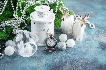 Scandinavian style Christmas or New Year decorations - white glass balls and toys, wooden decoration, floor lamp light, wooden deer and pocket whatches