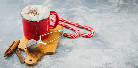 Christmas red enamelled cup with hot chocolate and whipped cream, cinnamon sticks, anise stars and hearty shortbread sugar cookies and candy canes on a light background. Space for text. long wide banner