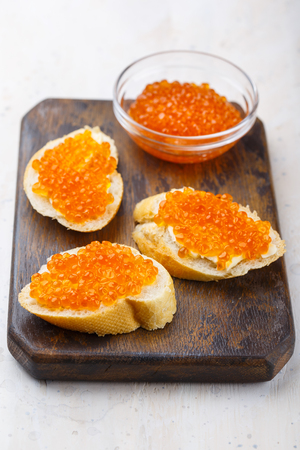Sandwiches with red caviar and butter in plate on wooden table. Top view Фото со стока
