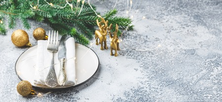 Festive place setting for christmas dinner on white rustic background. Christmas table setting with gold decorations on gray table. Holiday Decorations. Copy space. Stock Photo