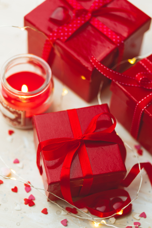 Gift red boxes with red bow ribbons, candles, lights garland and hearts on light background for Valentines day.