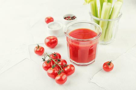 Glas köstlicher Tomatensaft mit zwei gestreiften Strohhalmen, frischem Sellerie, Salz, Pfeffer und frischen saftigen Kirschtomaten auf hellem Hintergrund. Bloody-Mary-Cocktail
