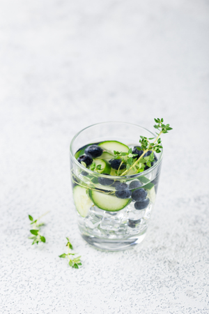 Detox infused flavored water with blueberry, cucumber and thyme on white background. Refreshing summer homemade cocktail Stock Photo