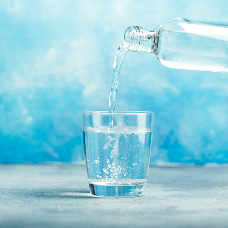 Pouring clear water from bottle into glass on blue background