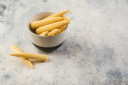 Fresh young baby corn on grey concrete background 写真素材