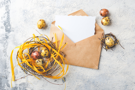 Colored yellow and brown Easter quail eggs with feathers in small nests and Greetings card in envelop. Shallow depth of field. Top view. Space for text.