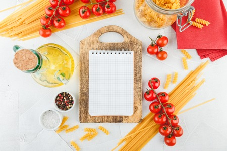 Notebook on wooden cutting board with different types of dry pasta and tomatoes on white wooden background, top view. Copy space. Flat lay.