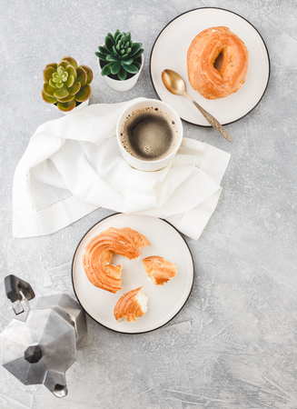 Breakfast with Cream puff rings - choux pastry, and cup of black coffee on a light background