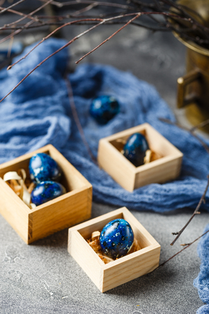 Easter eggs in wooden boxes painted in blue color. Quail eggs for catholic and orthodox easter holiday