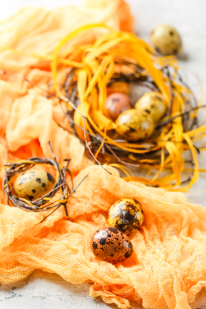 Colored yellow and brown Easter quail eggs in small nests. Shallow depth of field. 版權商用圖片