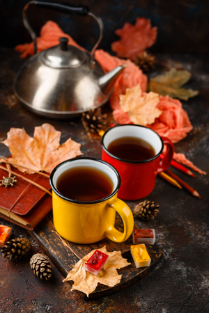 Two colored red and yellow enamel cups of tea, watercolors in cuvettes, colored pencils, autumn maple leaves and bumps on a rusty brown background Foto de archivo