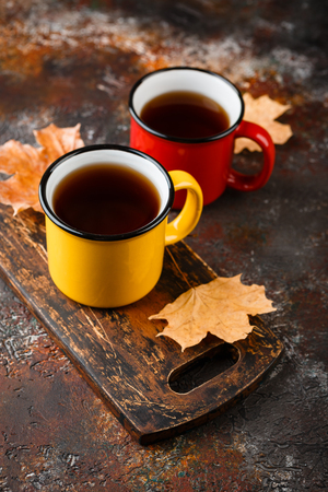 Two colored enamel tea cups, autumn maple leaves on rusty brown background 版權商用圖片