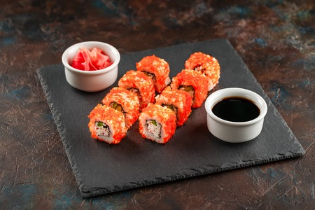 Japanese sushi rolls served on stone slate on dark background. Sushi rolls, maki, pickled ginger and soy sauce. Sushi background. Asian or Japanese food
