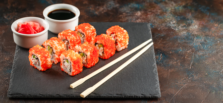 Japanese sushi rolls served on stone slate on dark background. Sushi rolls, maki, pickled ginger and soy sauce. Space for text. View from above. Sushi background. Asian or Japanese food. Long wide ban