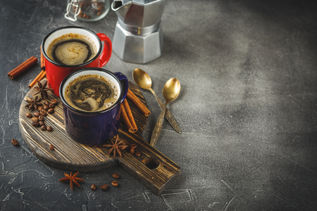 Red and blue enamelled cups of coffee, cinnamon sticks and anise stars on a gray background