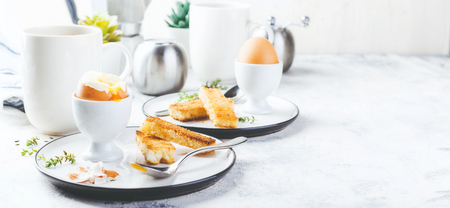 Soft boiled egg for breakfast with toasts and coffee cup in background. Space for text.Long wide banner Stock Photo