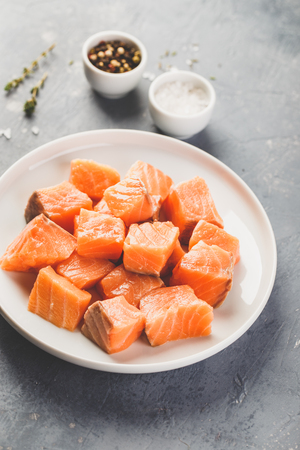 Diced pieces of salmon for marinating on white plate