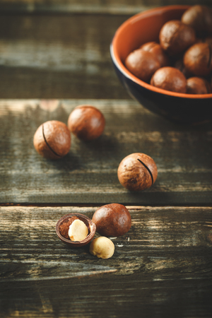 Organic Macadamia nuts in ceramic bowl on wooden table. Space for text