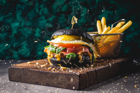 Beef burger with black bun, cheese, scrambled eggs, ham, tomatoes, arugula and chard and French fries on a wooden cutting board. Street food, fast food. Imagens