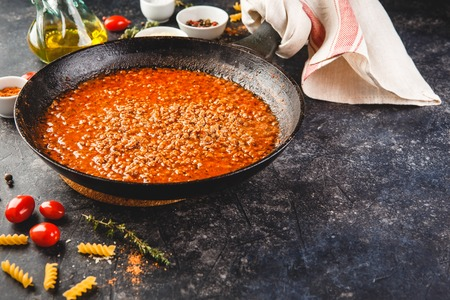 Classic italian bolognese sauce stewed in stewpot with ingredients on dark background